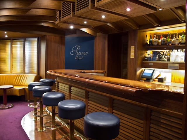 The Piano Bar is another Holland America Line staple.  Aboard Zaandam, her rich wood bar and ocean-blue seats create a truly nautical feel. Photo © 2011 Aaron Saunders